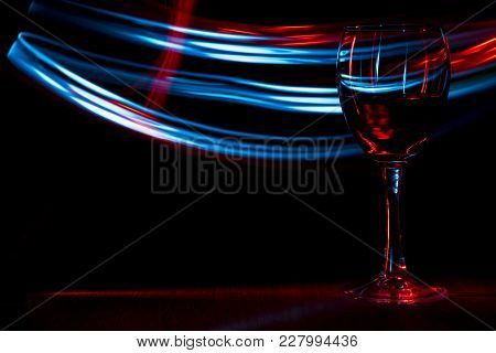 A Glass Of Wine In Night Club. Red And Blue Blurred Bands. The Light Effect.