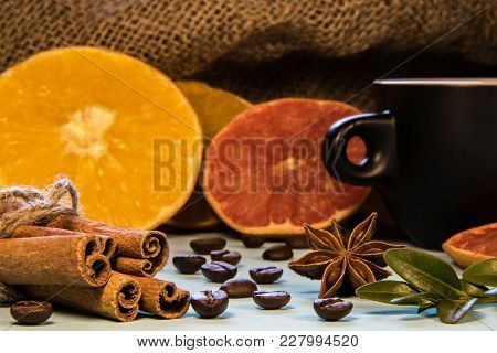 A Black Mug Of Coffee Next To Cinnamon With Puddings And Sliced Oranges With Green Coffe Leaws