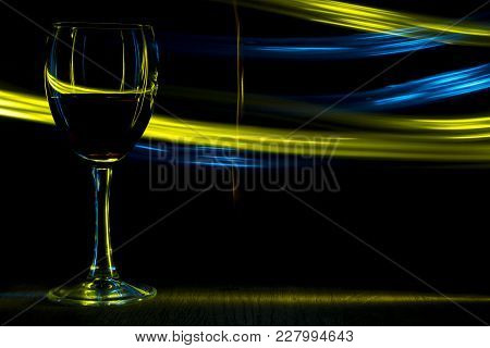 A Glass Of Wine In Night Club. Yellow And Blue Blurred Bands. The Light Effect.