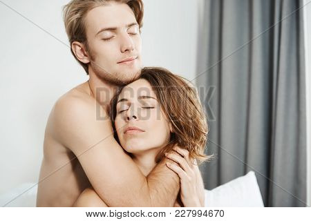 Close-up Shot Of Two Beautiful Tender Young Adults In Love, Hugging In Bed With Closed Eyes And Roma