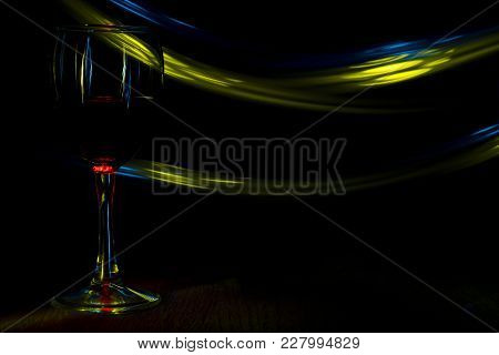 A Glass Of Red Wine In Night Club. Blue And Yellow Blurred Bands. The Light Effect.
