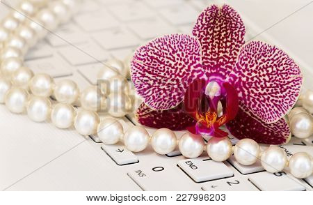 Female Online Business Concept - Beautiful Orchid Flower And White Pearls On Computer Keyboard