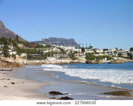 Clifton Beach In The Fore Ground, With Houses Across The Mid Ground And  Mountains In The Back Groun