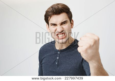 Fierce And Confident Stylish European Dark-haired Male Model With Trendy Haircut Holding Fist In Fro