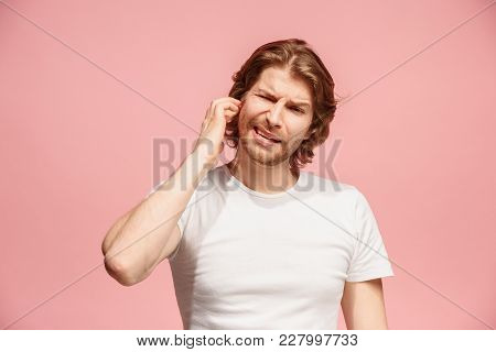 Sore Ear. Ear Ache Concept. The Sad Crying Man With Headache Or Pain On Trendy Pink Studio Backgroun