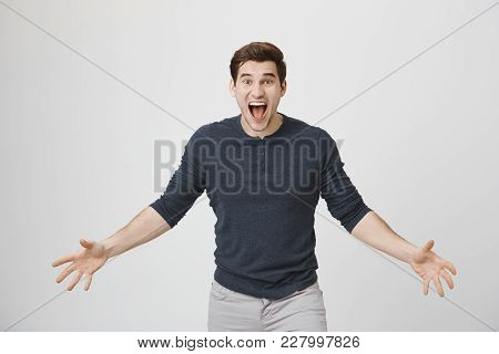Portrait Of Too Excited Young European Man, Spreading Arms And Shouting With Widen Eyes At Camera, S