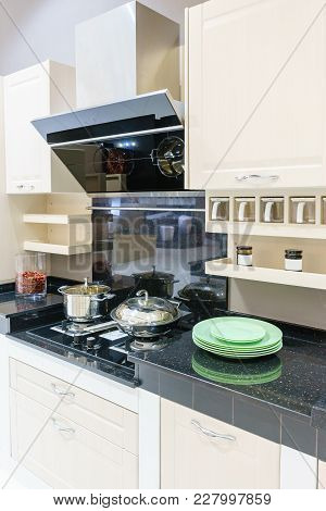 Modern Kitchen Furniture With Contemporary Kitchenware Like Hood, Black Induction Stove And Oven In