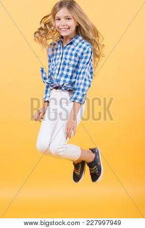 Happy Child Girl Jumping On Orange Background