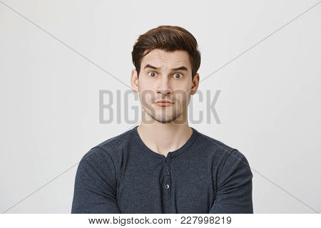 Handsome Young Guy Looking At Camera With Widen Eyes, Expressing Surprise And Astonishment While Sta