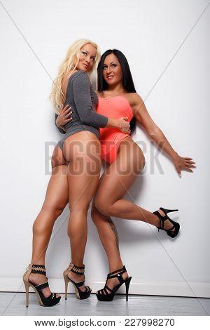 Two Sexy Women In Underwear Posing Over Light Wall.