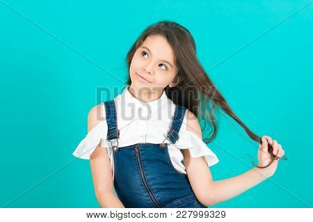 Kid Girl With Thinking Face Hold Long Brunette Hair On Blue Background. Haircare, Hairstyle, Hairdre