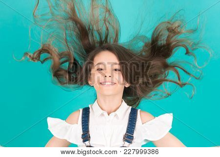 Girl Smile With Flying Hair On Blue Background. Child Smiling With Long Healthy Hair. Beauty Salon C