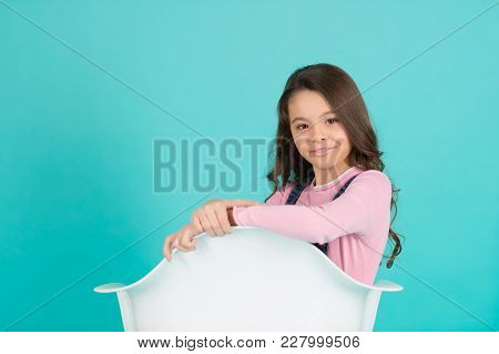Kid Pose In White Armchair On Blue Background. Little Girl With Adorable Smile And Long Brunette Hai