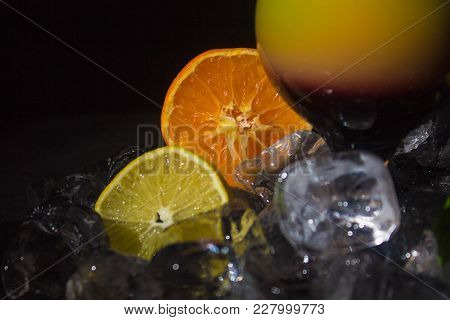Lemon And Orange Among Ice Cubes And Coctail