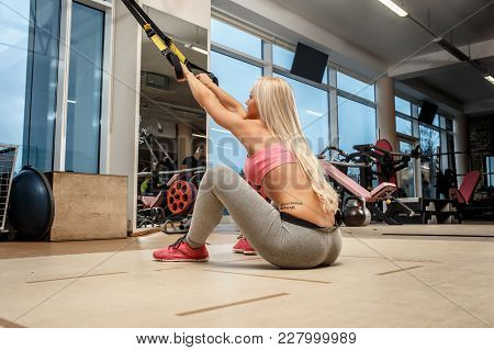 A Woman Sitting On The Floor In A Gym.