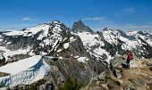 A Woman Hiker Views Thorton Peak and Mt Fury from the Summit of Trappers Peak. North Cascades National Park, Washington poster