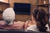 back view of woman eating popcorn while watching film together with manikin at home, perfect relationship dream concept poster