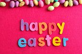 The words happy easter displayed with speckled easter candy eggs on a pink background poster