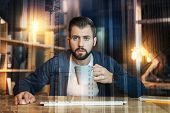 Attentive look. Calm enthusiastic clever worker holding a cup of tea and looking attentively at the screen while sitting alone late in the evening poster