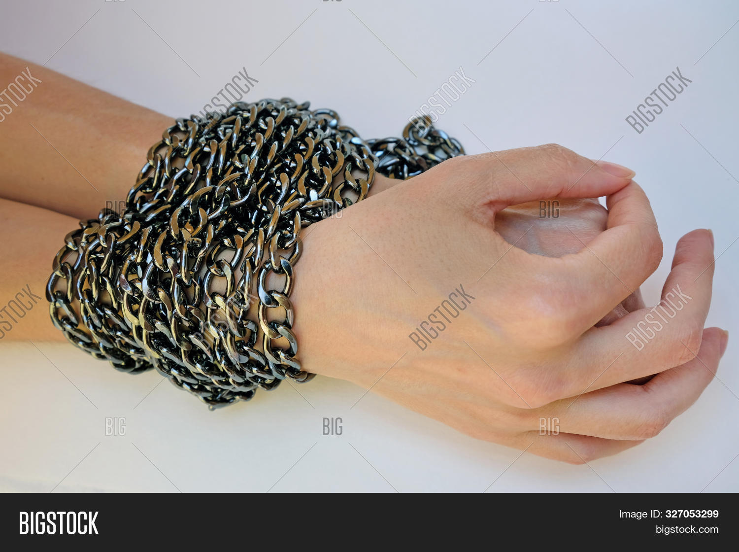 Female Hands Tied With A Black Chain Close-up. The Concept Of Violence Against Women And The Infring