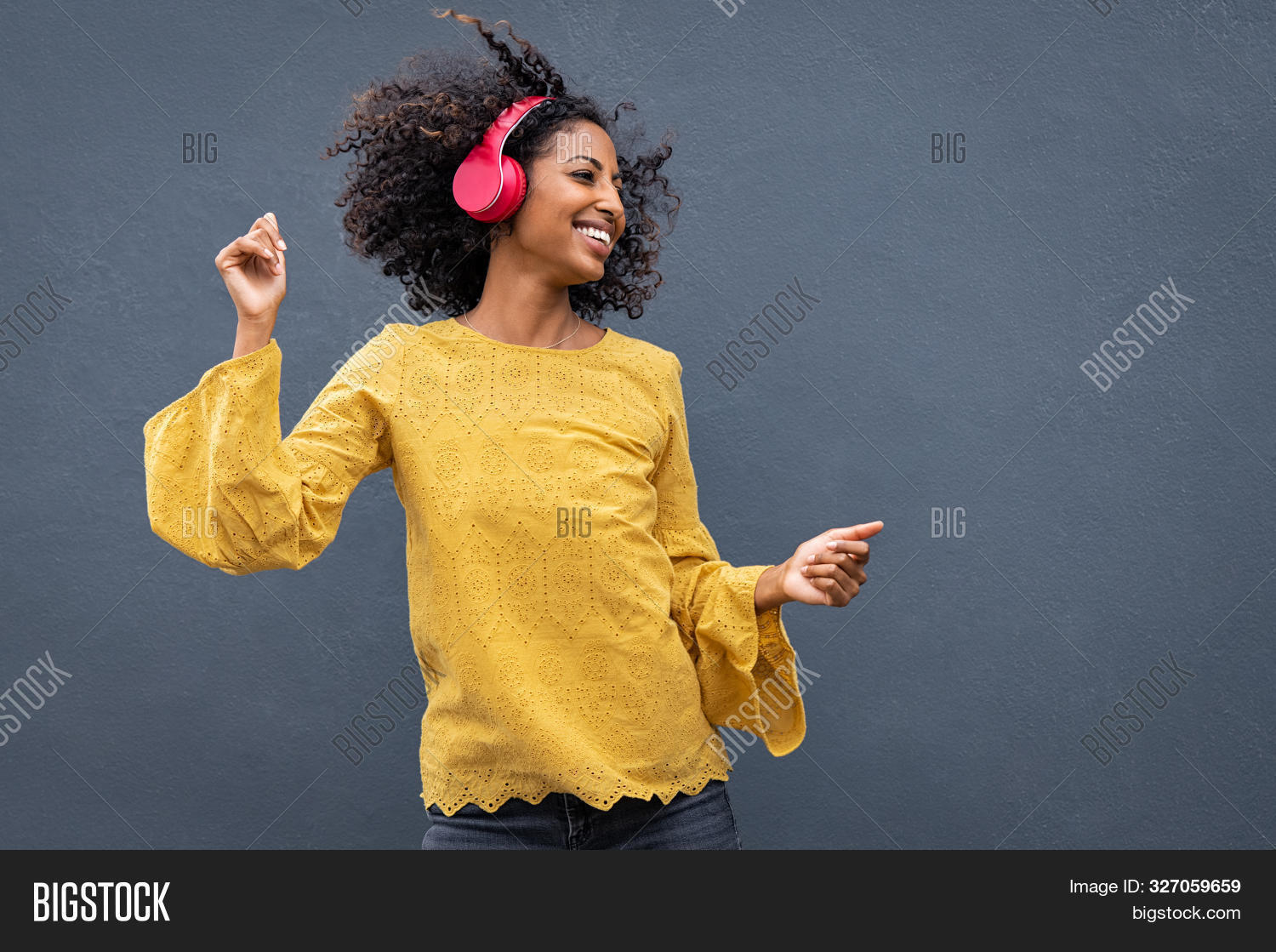 Beautiful black girl listening music. Cheerful young woman with curly hair making dance moves to the rhythm of music while listening through wireless headphones isolated on grey wall.