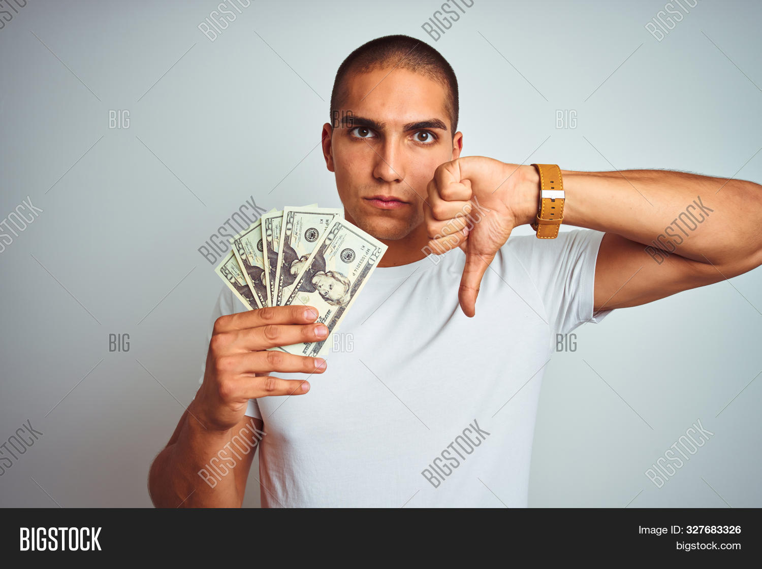 Young handsome man holding dollars over white isolated background with angry face, negative sign showing dislike with thumbs down, rejection concept