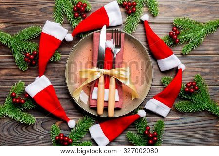 Holiday Composition Of Plate And Flatware Decorated With Santa Hat On Wooden Background. Top View Of