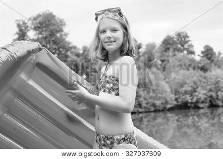 Black and white photo of smiling girl in swimwear standing with pool raft at lakeshore