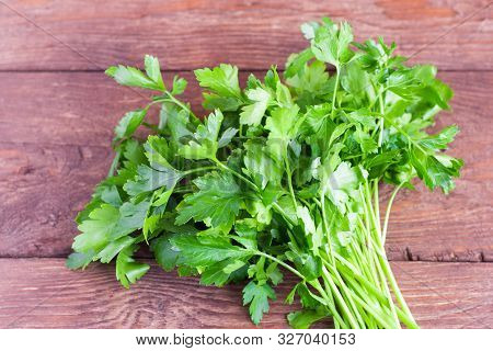 Bunch Of Fresh Parsley On The Background Of A Wooden Table. Fresh Parsley On A Wooden Background. Pa