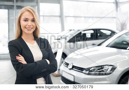 Smiling Female Car Dealer With Folded Arms Looking At Camera And Posing In Front Of New Automobiles.