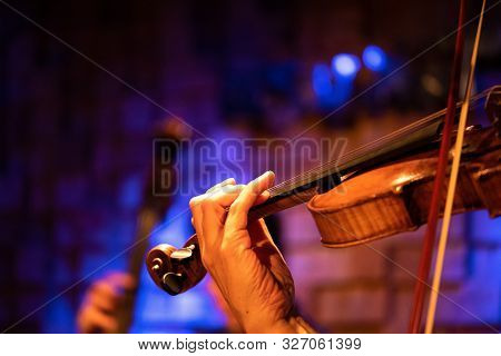 A Violinist Plays Classical Music On A Violin At A Concert With An Orchestra.