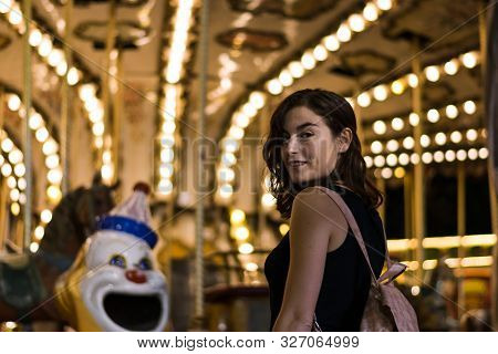 Young Woman In A Fair, Carousel Lights In The Background