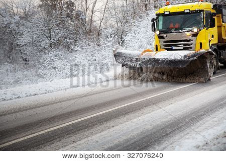 Truck Cleaning On Winter Road Covered With Snow
