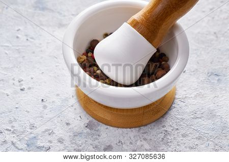 Pounder With Mix Of Different Spices Peppers On White Background.