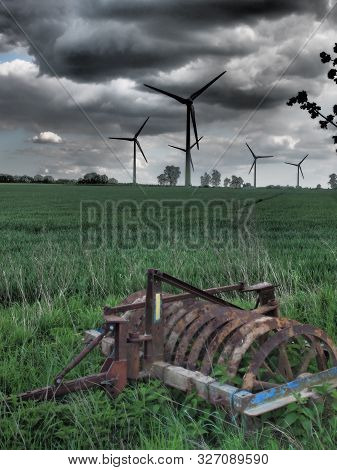 Wind Power Turbines In Agricultural Area East Of Hamburg, Germany In Dramatic Tones