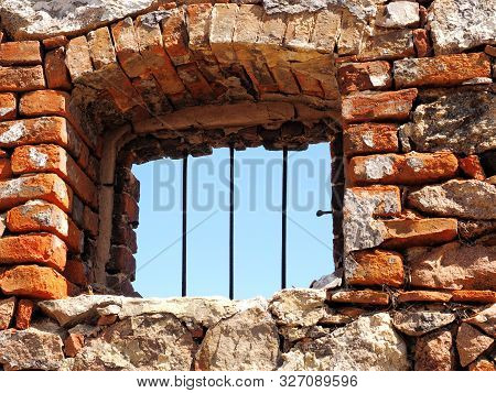 Window With Iron Bars In A Rough Wall Made Of Natural Stone And Boulders