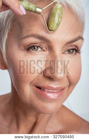 Close Up Of A Face Of Aged Woman Rolling Jade Roller On Her Fore Head