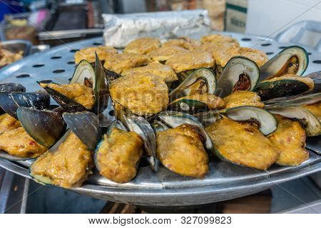Chon Buri, Thailand - March 16, 2019: Closeup Of Heap Of Fried Mussels In Yellow Dough On Display At