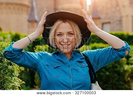 Portrait Young Beautiful Fashionable Happy Woman In A Black Hat. Girl Posing Street Against Backgrou