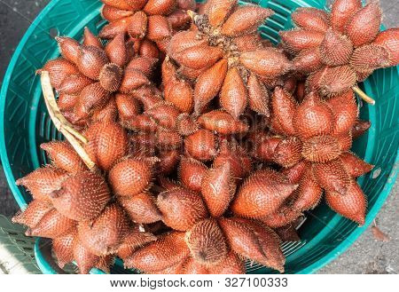 Chon Buri, Thailand - March 16, 2019: Closeup Of Azure Basket Filled With Red-brown Snake Fruits On