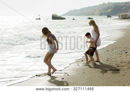 Family Play With Waves At Beach, Enjoying Togetherness