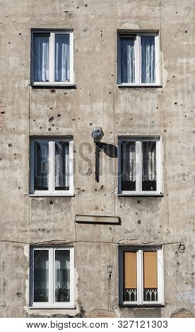 Old tenement in capital of Poland Warsaw in Praga district with second world war marks of shots on its parget poster