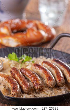 Closeup Of Grilled Nuremberger Bratwurst With Sauerkraut