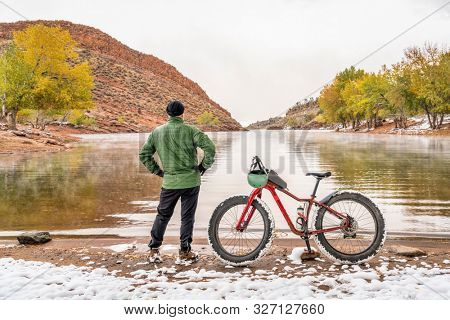 senior male cyclist with a mountain fat bike on a lake shore in fall scenery, Horsetooth Reservoir in foothills of northern Colorado