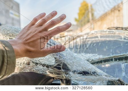 A Man's Fist Against The Broken Windshield. Cracks On The Windshield Of The Car From The Impact