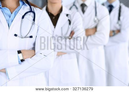 Group Of Modern Doctors Standing As A Team With Arms Crossed In Hospital Office. Physicians Ready To