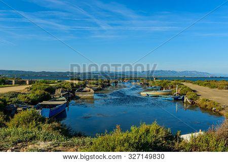 Boat on a Canal in Ebro Delta estuary and wetlands, Tarragona, Catalunya, Spain. poster