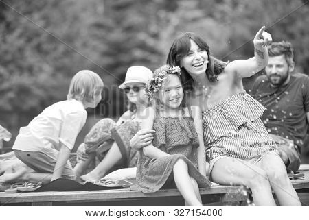 Black and white photo of Smiling woman pointing to daughter while sitting on pier against family at lakeshore during summer