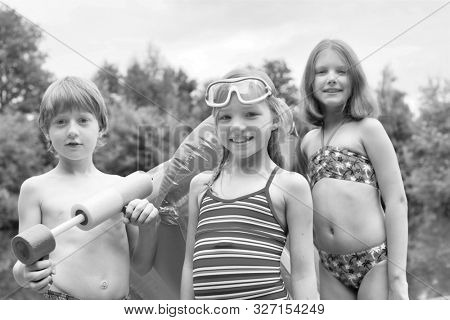 Black and white photo of smiling friends in swimwear standing with pool raft and squirt gun at lakeshore
