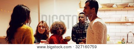 Side view of a group of young adult multi-ethnic male and female friends socialising in the kitchen of an apartment, talking together and drinking coffee
